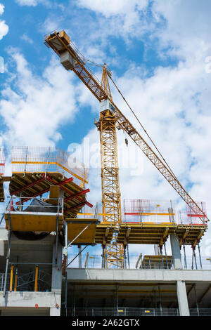 Construction of an apartment building in the center of a large city with the help of a construction crane. Photo taken from below. - Stock Photo