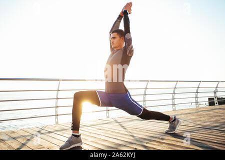 Yogi man practicing yoga exercises at sunrise - Stock Photo