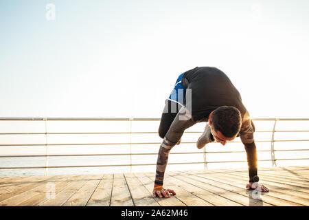 young man doing a bakasana, crane pose during an intense yoga practice - Stock Photo