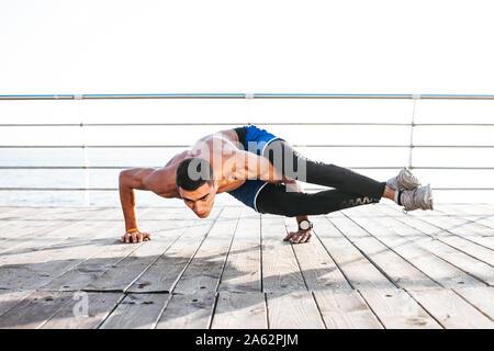 sporty muscular young yogi man doing backbend exercises
