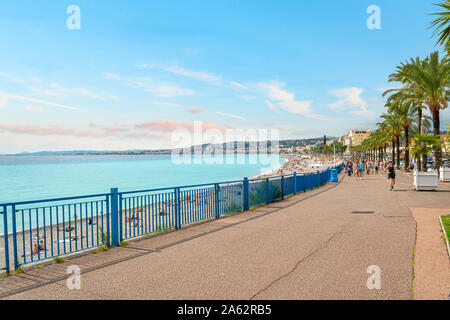 Joggers and walkers pass the Mediterranean sea and beach along the Promenade des Anglais on the French Riviera in Nice France - Stock Photo