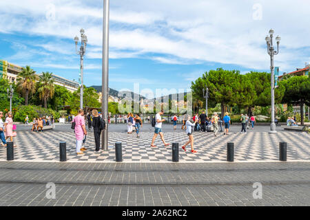 Tourists enjoy a pleasant day on the French Riviera as they stroll Place Massena with Promenade du Paillon water park in the distance in Nice France - Stock Photo
