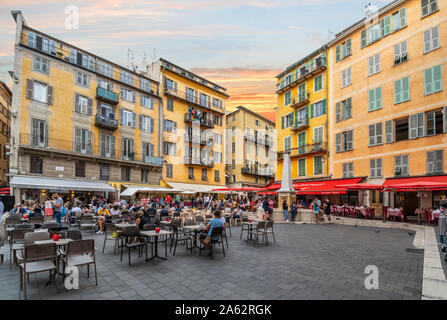 Tourists and locals enjoy an early evening at the cafes, the water fountain, and shops in Place Rossetti, one of the main piazzas in Vieux Nice France - Stock Photo