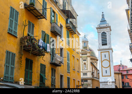 View of the campanile bell tower of the Nice Cathedral at Place Rossetti past an apartment building with laundry hanging in Old Town Nice France. - Stock Photo