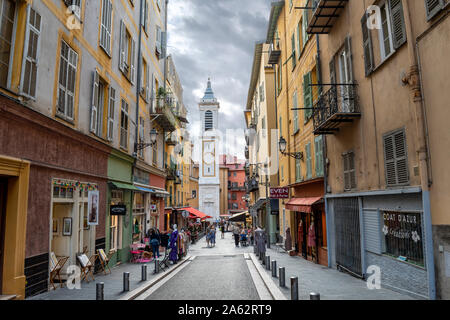 View of the campanile bell tower of the Nice Cathedral at Place Rossetti as tourists enjoy the late afternoon in Nice, France. - Stock Photo