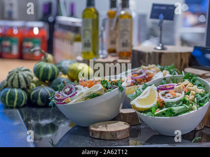 salad bar with bowls with onions and lemon rucola and pumpkin in the background as well as olive oil and other sauces - Stock Photo