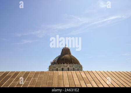 Rooftop view of the dome of the Baptistry of St John in the famous Piazza dei Miracoli in Pisa against a clear blue sky background, Tuscany, Italy - Stock Photo