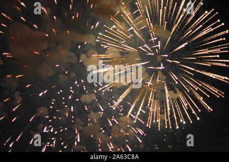 Inexpensive fireworks, over the city, yellow and blue . Selective focus. For any purpose. - Stock Photo
