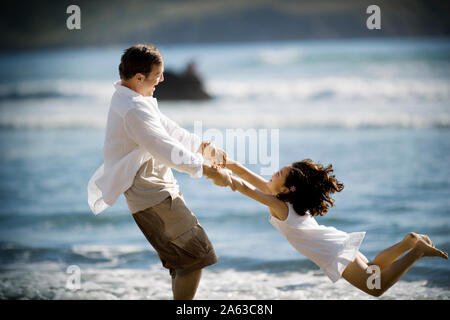 Smiling father swinging her daughter around by her arms near the water on a beach in the sunshine. - Stock Photo