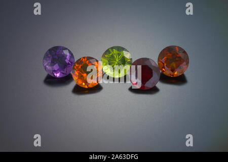 A round cut amethyst, citrine, peridot, red garnet and a fire citrine are shown on a grey reflective background. - Stock Photo