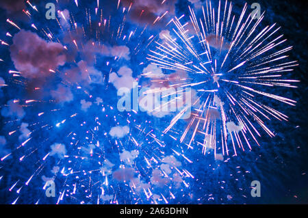 Inexpensive fireworks, over the city, red and blue . Selective focus. For any purpose. - Stock Photo