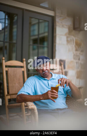 Senior man sitting in a wicker chair on a porch holding a drink. - Stock Photo
