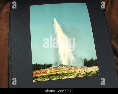 Nice and vintage album containing early Photochrom style colorized photographs of Yellowstone National Park. - Stock Photo