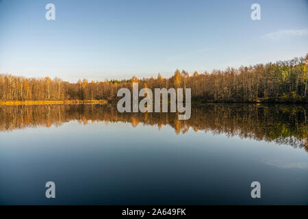 The autumn forest surrounds a beautiful forest lake on the surface of which the blue sky is reflected - Stock Photo