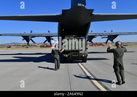 U.S. Air Force 29th Weapons Squadron instructor loadmasters guide a U.S. Army High Mobility Artillery Rocket System onto a C-130J Hercules at Guernsey Airport, Wyoming, Oct. 14, 2019. The 29th WPS relies on the assistance of loadmasters, of which there is a coinciding course -- the Loadmaster Advanced Instructor Course. This strengthens the necessary bond between pilot and loadmaster, allowing full understanding and communication on what is going on in the back of the aircraft. (U.S. Air Force photo by Airman 1st Class Aaron Irvin) - Stock Photo