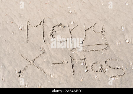 Merry X-Mas written in the sand at beach in Florida. Christmas in the sun concept. Seasons greetings. Sand with shells. - Stock Photo