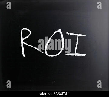 'ROI' handwritten with white chalk on a blackboard. - Stock Photo