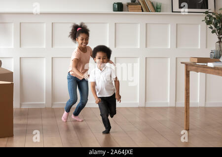 Excited preschooler kids have fun running at home - Stock Photo