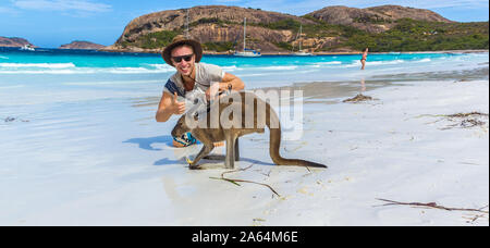 caucasian man with a beautiful Kangaroo at Lucky Bay Beach in the Cape Le Grand National Park near Esperance, Australia - Stock Photo