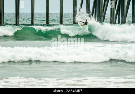 Experienced surfer shredding a large wave at Huntington Beach, California, also known as Surf City USA, home of the U.S. Open of Surfing. - Stock Photo