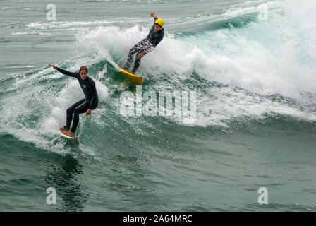 Senior surfer and a younger rider sharing a wave at Huntington Beach, California, also known as Surf City USA, home of the U.S. Open of Surfing. - Stock Photo