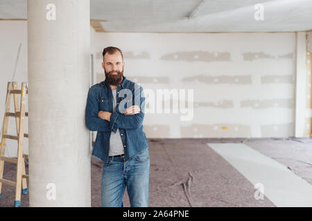 Young bearded man standing with folded arms leaning against a pillar in an unfinished new build house looking thoughtfully at the camera - Stock Photo