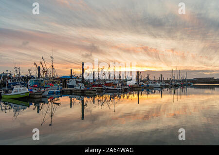 Newlyn, Cornwall, UK. 24th October 2019. UK Weather. Early morning clouds starting to left at sunrise over Newlyn Harbour. Tomorrow sees the return of strong winds and heavy rain. Credit Simon Maycock / Alamy Live News. - Stock Photo