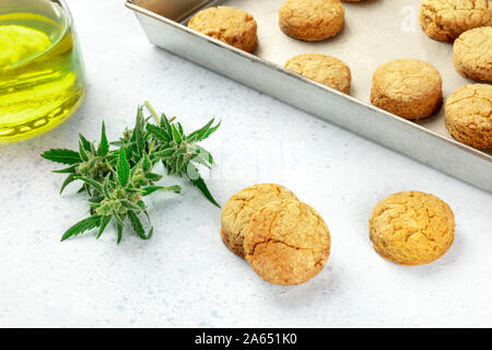 Cannabis butter cookies with marijuana buds and cannaoil, homemade healthy biscuits - Stock Photo