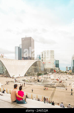 young couple on the stairs of la grande arche - Stock Photo