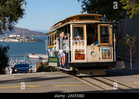 SAN FRANCISCO, USA - OCTOBER 2, 2019:  People travelling on the Powell and Hyde cable car on Hyde Street with Alcatraz Island and Fishermans Wharf beh - Stock Photo