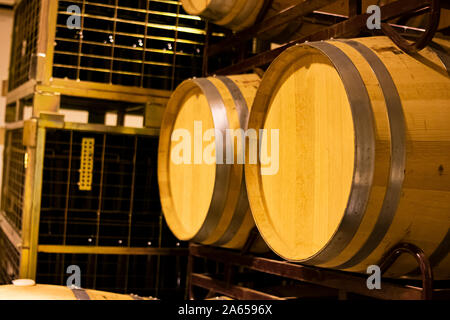American oak barrels for aging and aging of wine in a cellar stacked on metal shelves - Stock Photo