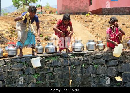 Children collecting water from well at Dhakne village, Shahapur Thane Maharashtra, India, Asia - Stock Photo