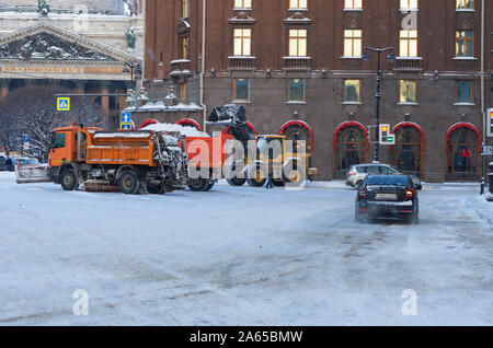Winter morning tractor loads snow in a dump truck next to a snowplow near St. Isaac's Cathedral (St. Petersburg, Russia) - Stock Photo