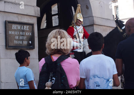 A mounted soldier of the Queen's life guards at Horse guards Parade, Whitehall, London, with a mother and her two sons observing - Stock Photo