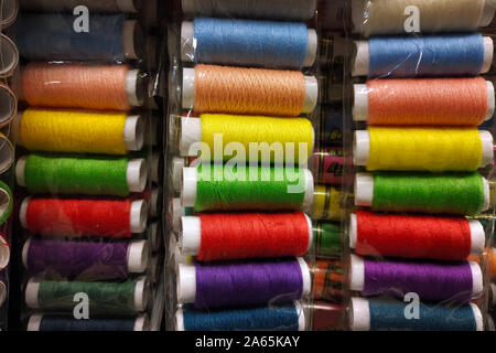 Multi-colored sewing threads close-up. Skeins of thread of different colors on the counter in the store. Threads for sewing. - Stock Photo