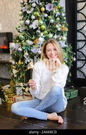 Young happy woman wearing jeans sitting with bengal light near Christmas tree. - Stock Photo