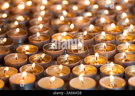 Burning tealight candles close-up. Many lit tea light flames spread for Diwali. Beautiful table top decoration for Hindu festival of lights or for Chr