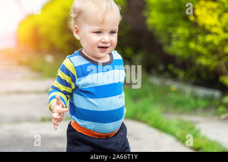 Cute little toddler boy showing mother dirty hands after playing in mud outdoors. Curious child with dirt or soil on palms after discovering world