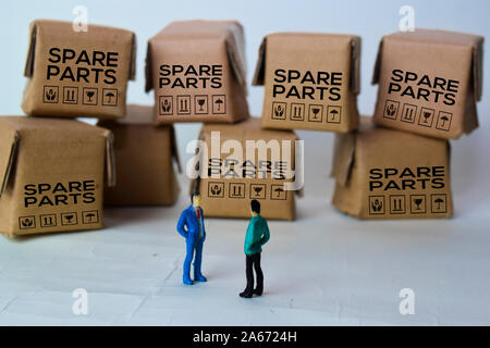 Miniature businessman Talking in front of Boxes with text Spare Parts isolated white bakground - Stock Photo