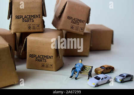 Miniature businessman sitting on Boxes with text Replacement Parts isolated white bakground - Stock Photo