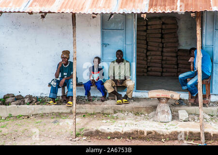 Gambian men and a boy sitting outside a cement store in Senegambia. - Stock Photo