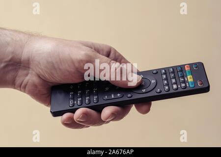 Male hand with a TV remote control close-up. The man turns on the TV