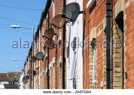 Looking up at satellite  dishes on terraced housing at Portland in Dorset, England, UK - Stock Photo