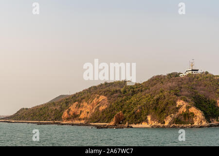 Laem Chabang seaport, Thailand - March 17, 2019: White building of port control and operation center in brown-green hills above the harbor with antenn - Stock Photo