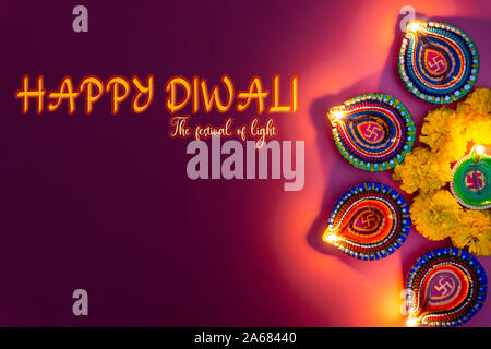 Indian festival Diwali, Diya oil lamps lit on colorful rangoli. Hindu traditional. Happy Deepavali. Copy space for text. - Stock Photo