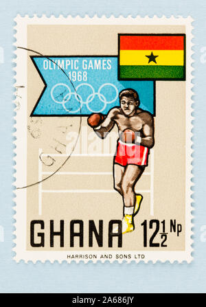Close up of Ghana postage stamp celebrating the Olympic games in Mexico in 1968. Stamp with Ghana flag and boxer, on blue background with copy space. - Stock Photo