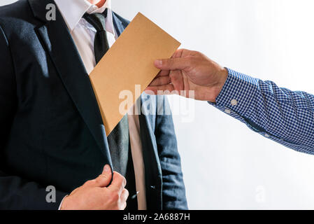 A man giving bribe money in a brown envelope to another businessman in a corruption scam. Bribery and corruption concept. - Stock Photo