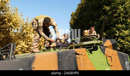 Strasbourg, France - Sep 21, 2019: Soldiers helping kid to put military helmet on the French armoured personnel carrier in central Place Broglie during French Army Open Days - Stock Photo
