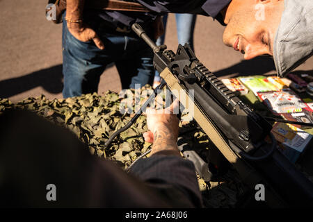 Strasbourg, France - Sep 21, 2019: Man admiring semi-automatic rifle at the open days of French Army exhibition on the street - Stock Photo