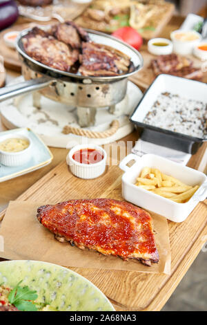 Barbecue pork spare rib. Grilled pork baby ribs with spicy bbq sauce. Barbecue restaurant menu. Many different food on the table. Dinner party or - Stock Photo